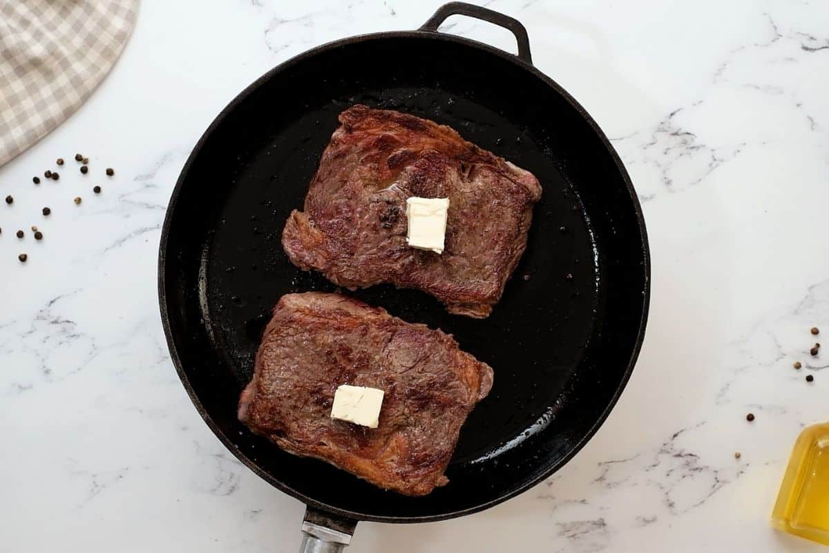 Steak in cast iron skillet with pats of butter.