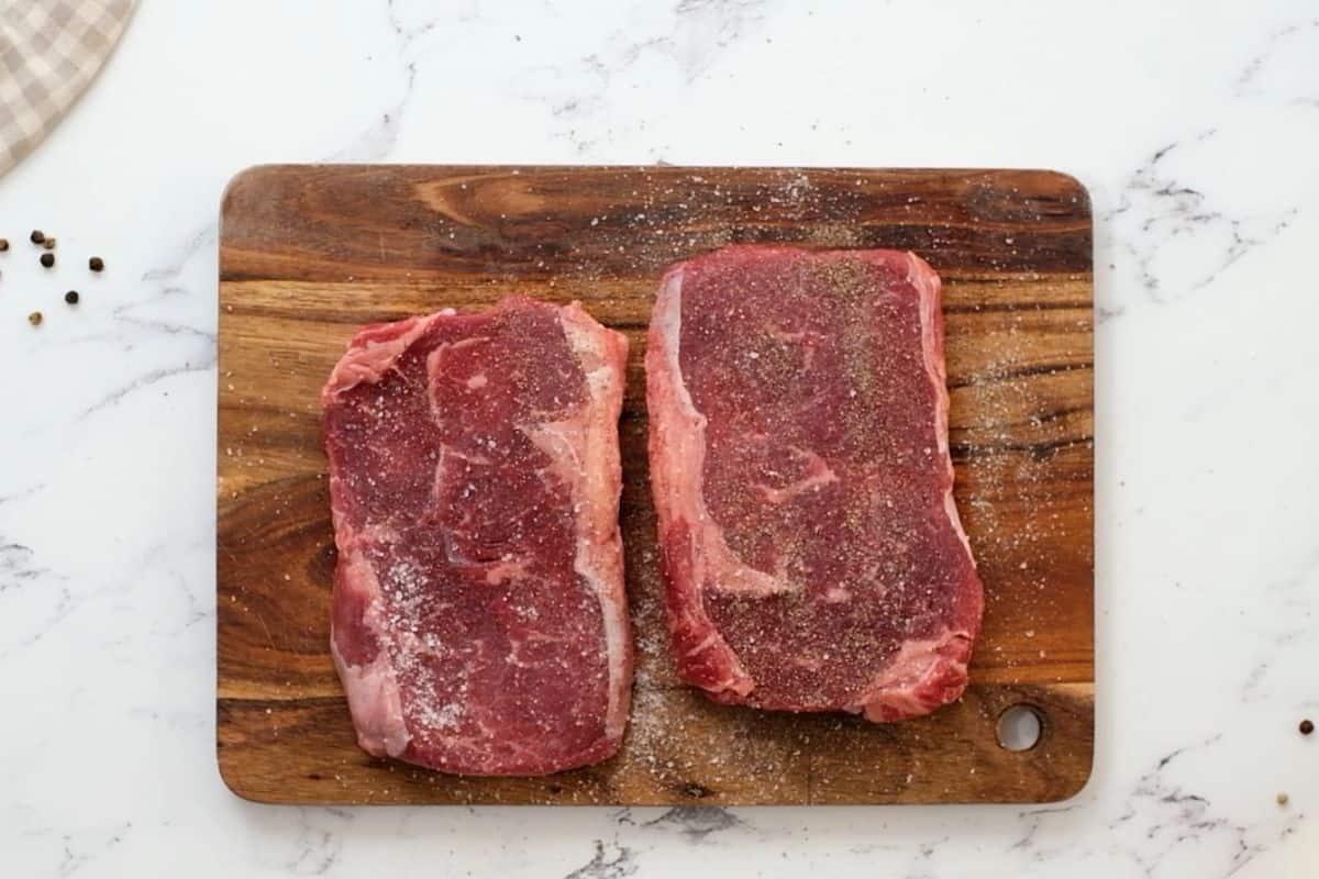 Seasoned ribeye steaks on wooden cutting board.