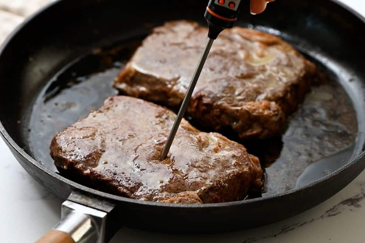 Steak with digital thermometer inserted into center.