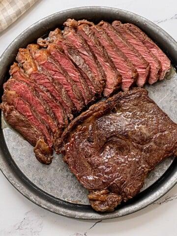 2 ribeyes on platter; one sliced, on seared.