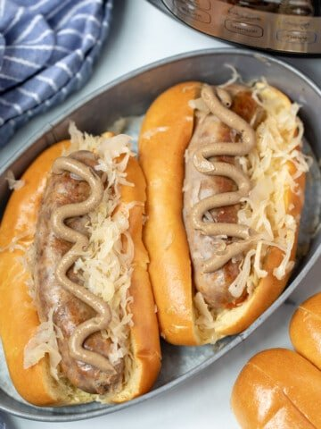 Two bratwurst in buns with sauerkraut and mustard next to instant pot.