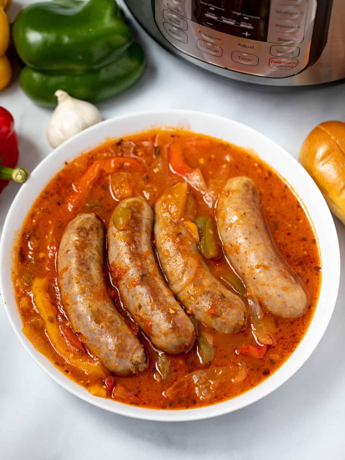 White bowl with Italian Sausage, peppers, onions, in tomato sauce next to instant pot.