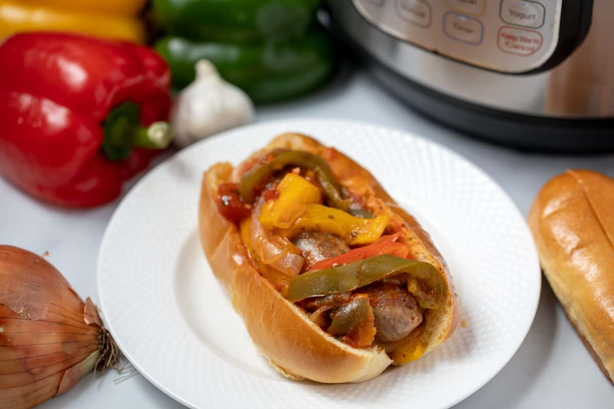 Italian Sausage topped with peppers, onions, on hoagie bun next to instant pot.
