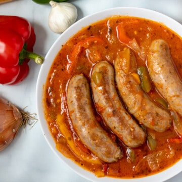 Sausage and Peppers in white serving dish next to peppers, garlic, and onions.