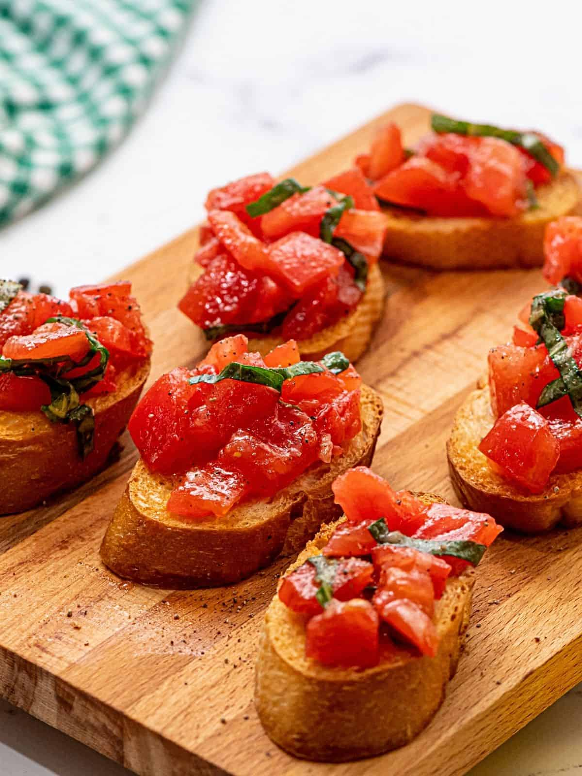 Prepared tomato bruschetta on wooden cutting board.