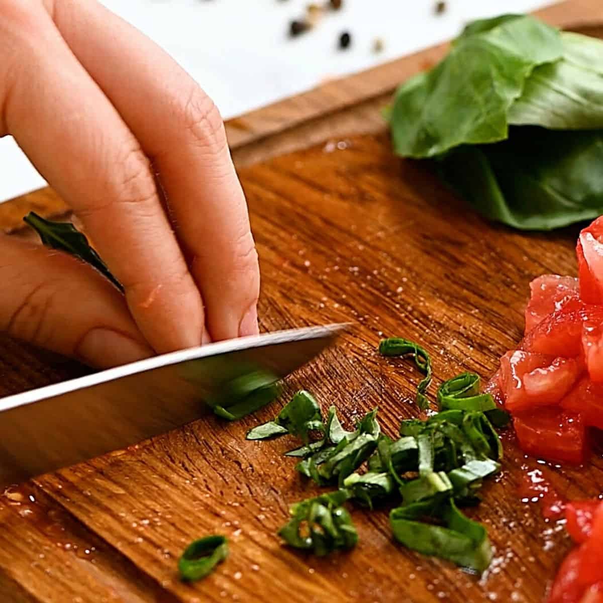 Slicing basil into ribbons on cutting board.