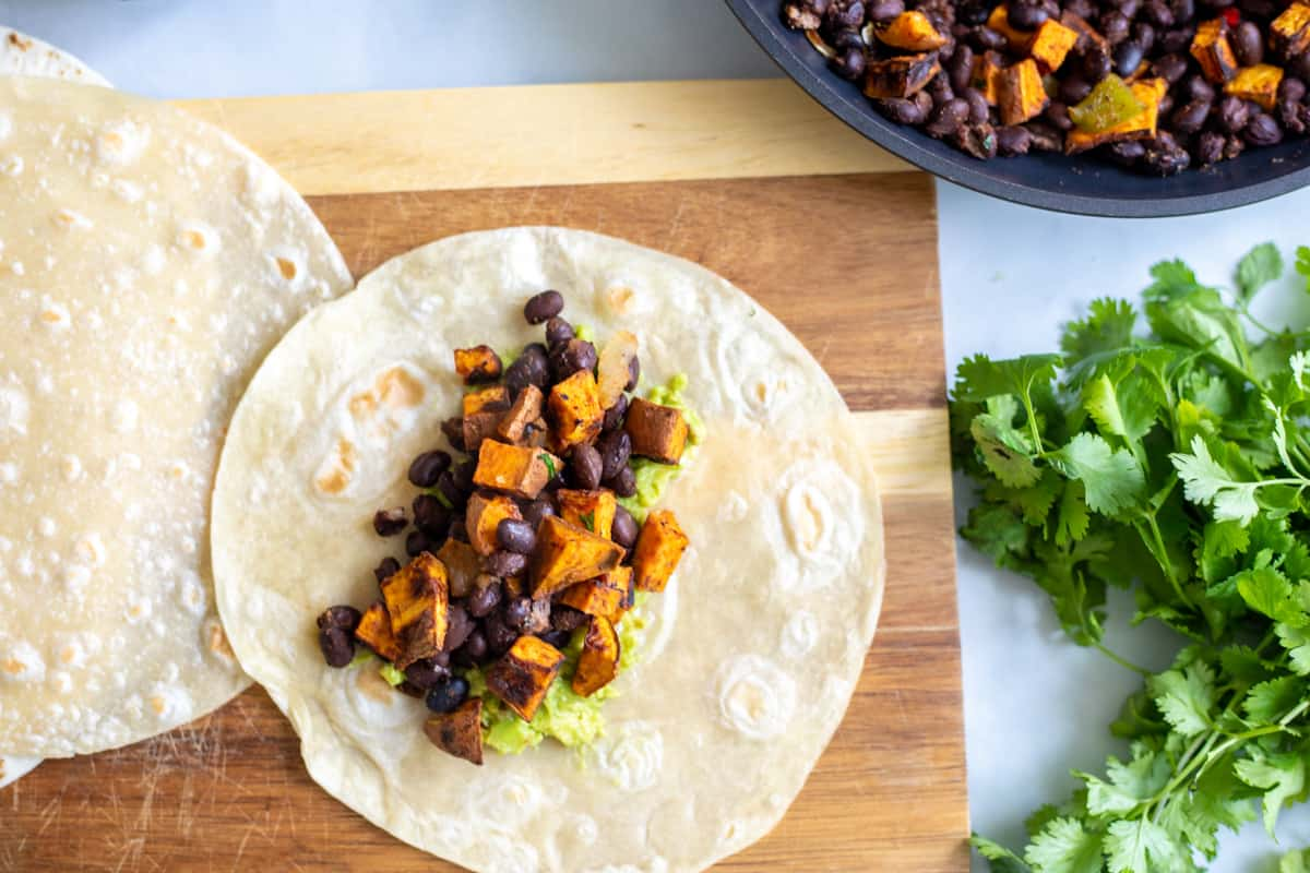 Flour tortilla topped with sweet potatoes and black beans.
