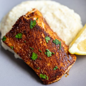 Blackened Mahi Mahi on plate with grits.