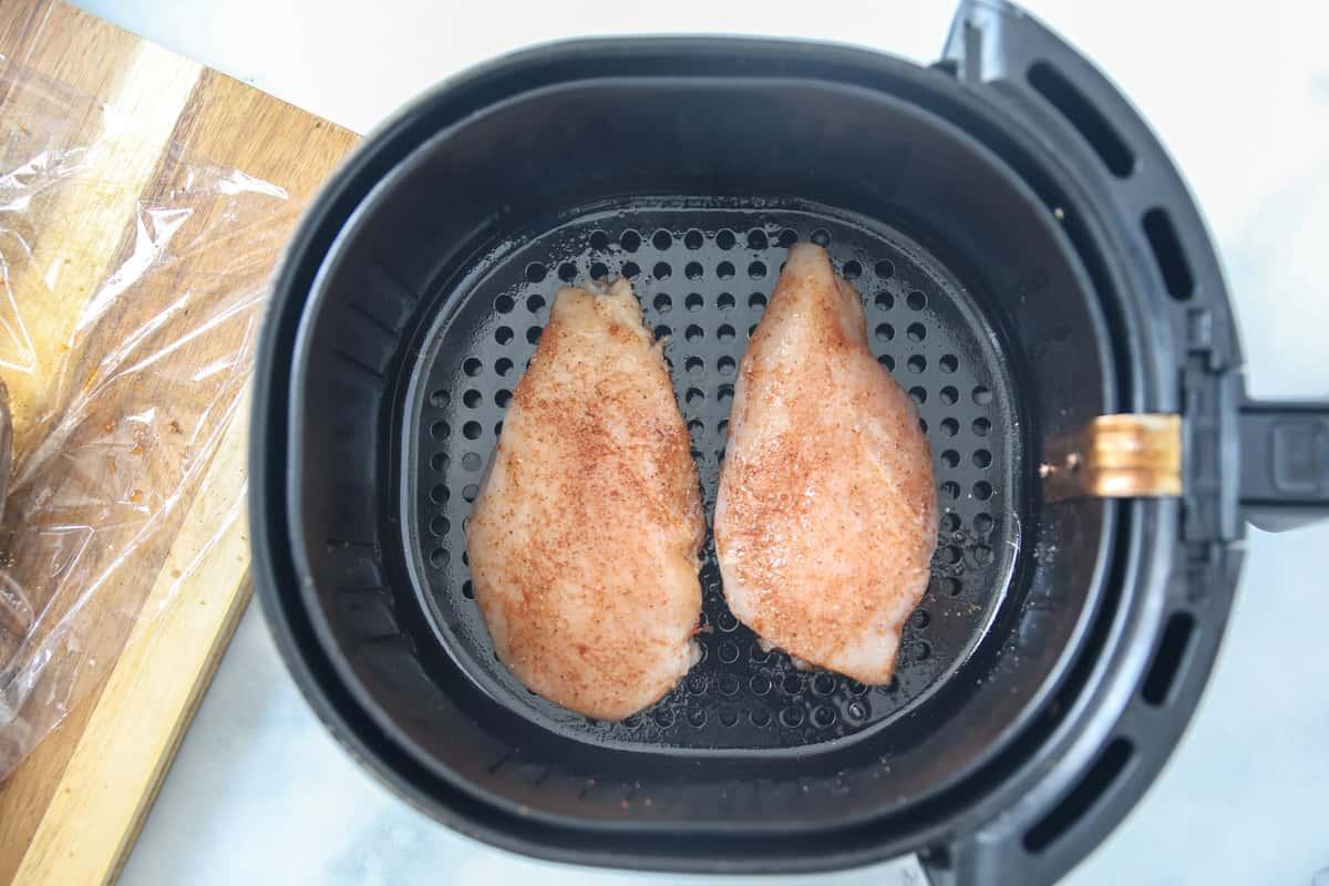 2 seasoned chicken breasts in air fryer basket.