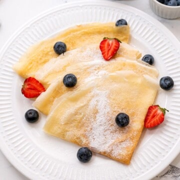 Crepes on white plate with fresh berries.