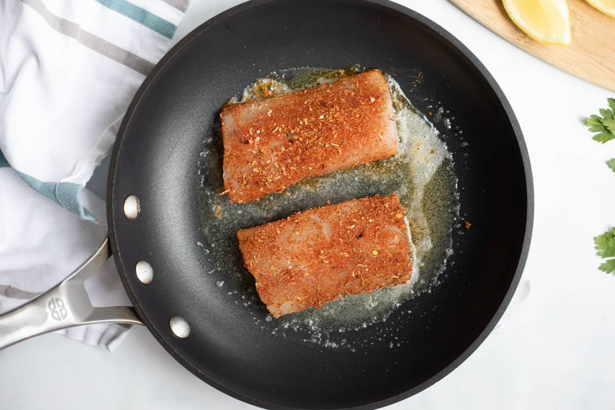 Mahi mahi fillets iin skillet with butter and oil.