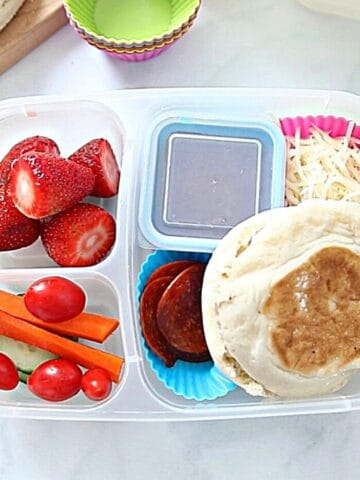 Lunch container with homemade pizza lunchable and fruits and veggies.