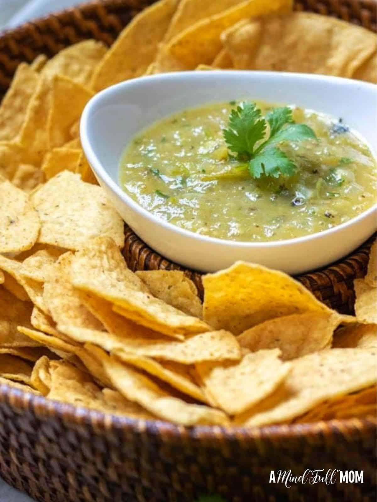 Bowl of homemade salsa verde next to tortilla chips.