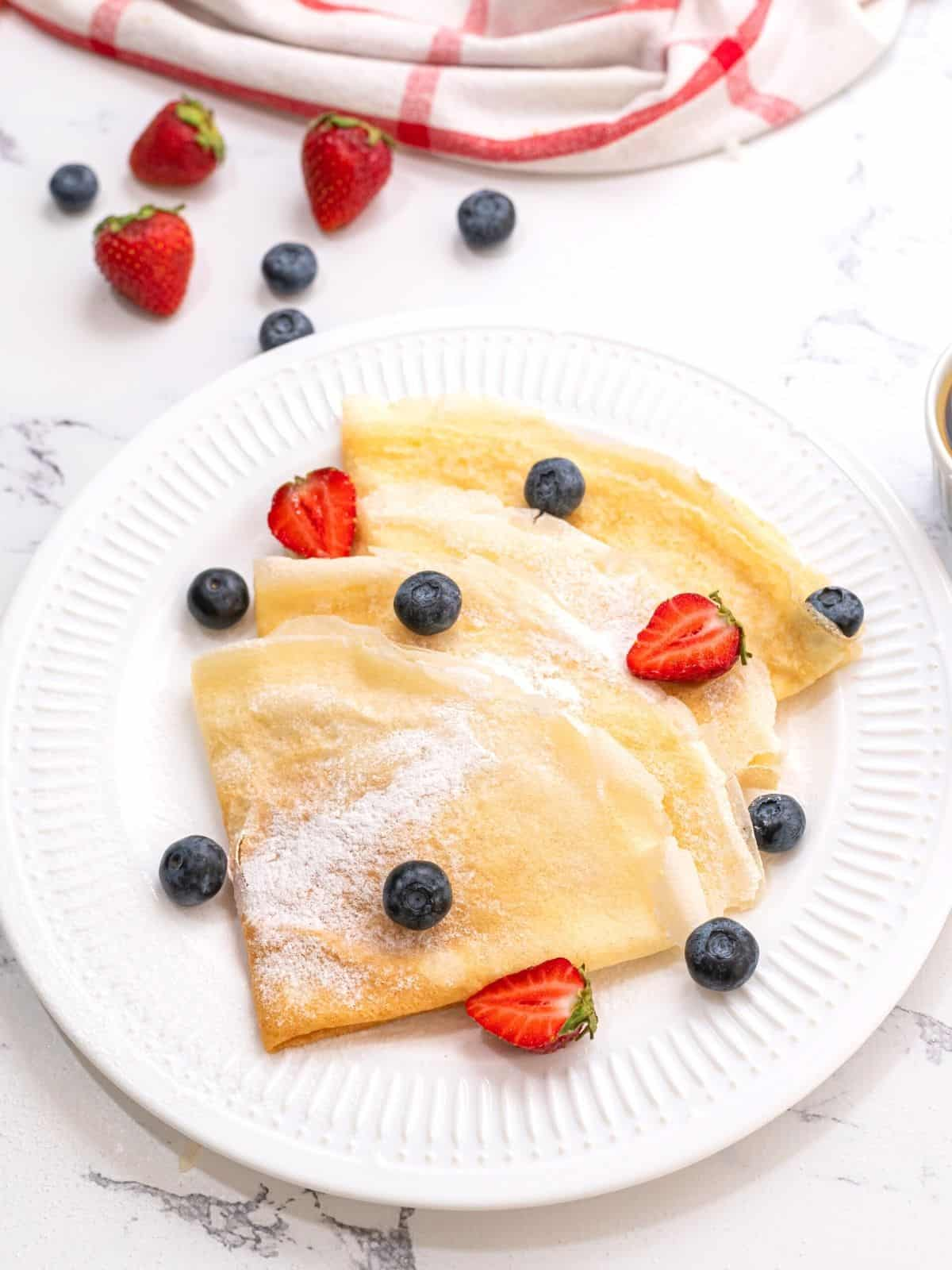 4 crepes folded on white plate topped with powdered sugar and berries.