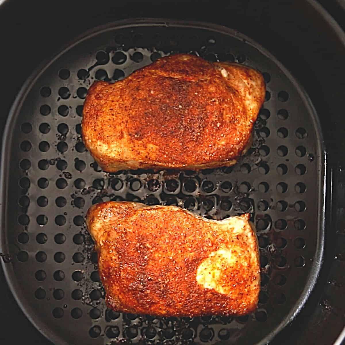 AIr fried pork chops in air fryer basket.