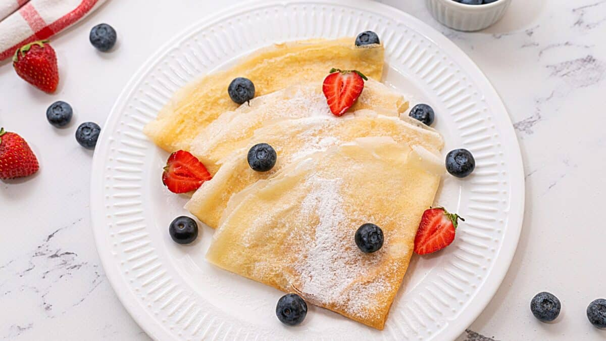 Crepes on a white plate topped with berries.