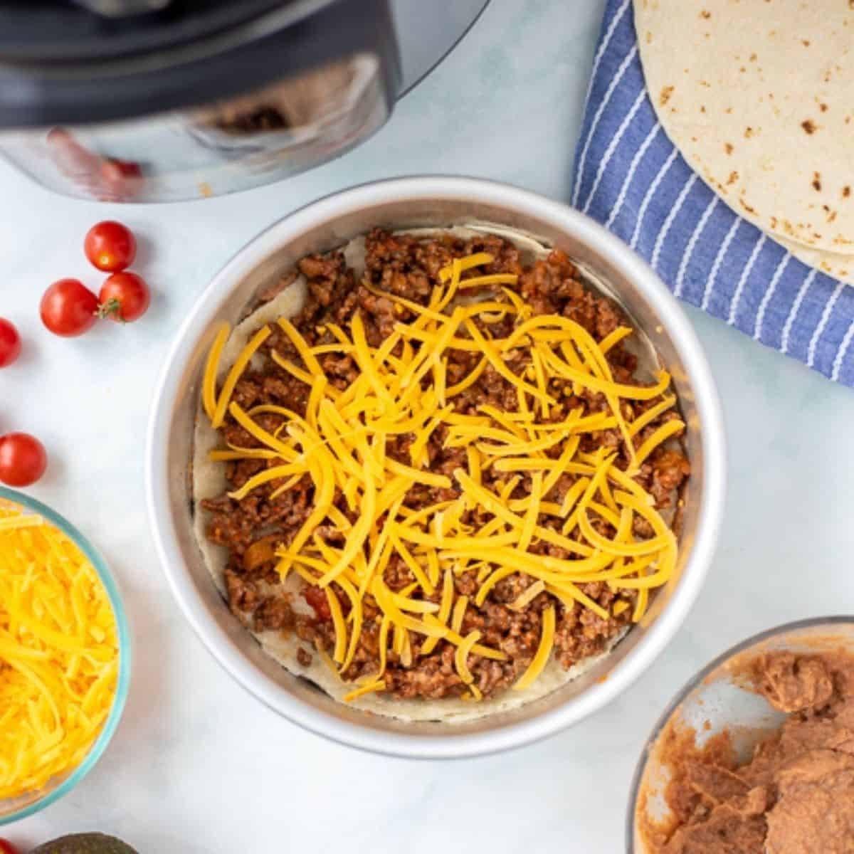 Layer of taco pie with taco meat and cheese in cake pan.