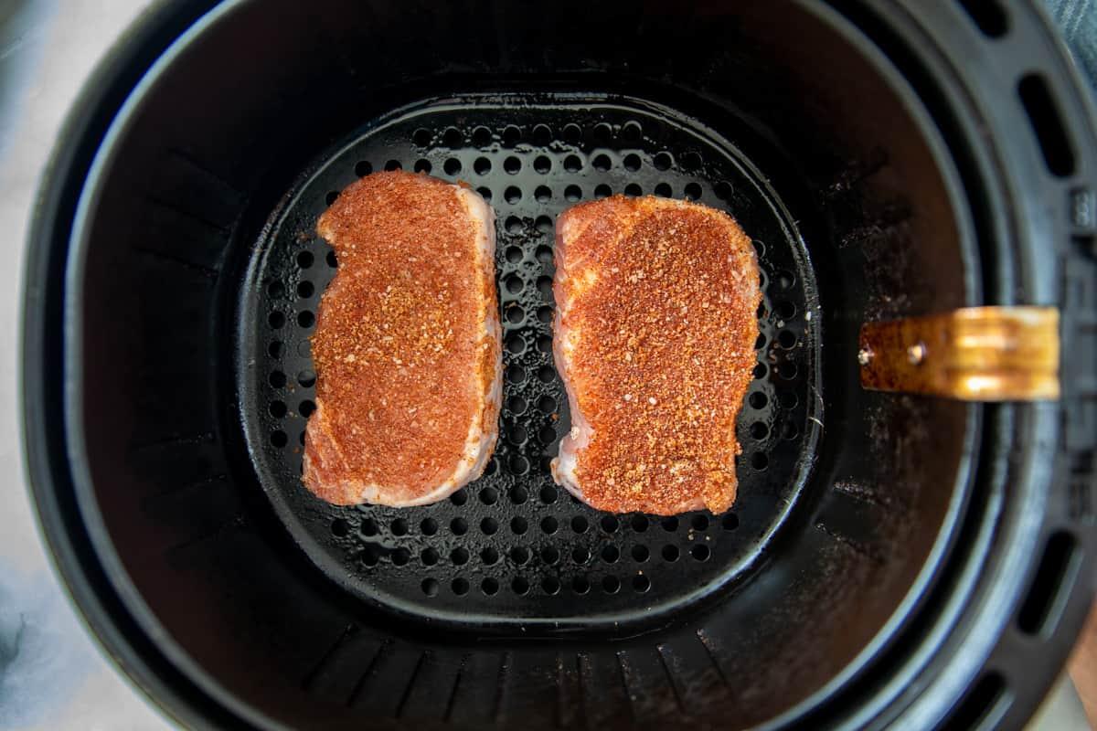 2 seasoned pork chops in air fryer basket.
