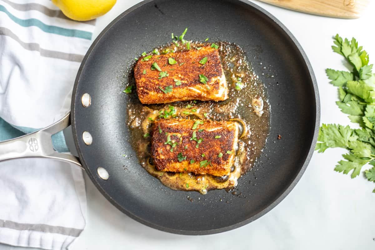 2 cooked mahi mahi fillets in skillet with parsley flakes.