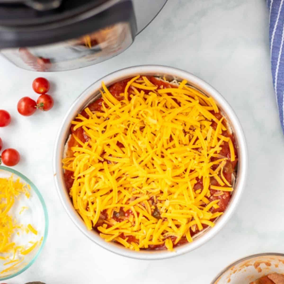 Assembled Taco Lasagna in cake pan next to instant pot.