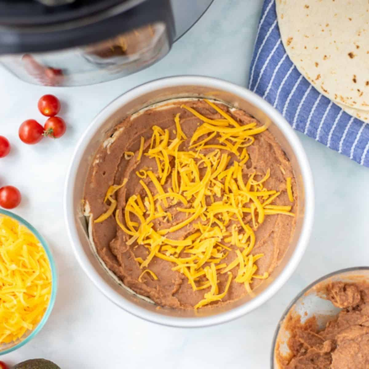Refried beans and cheese on tortilla next to Instant Pot.