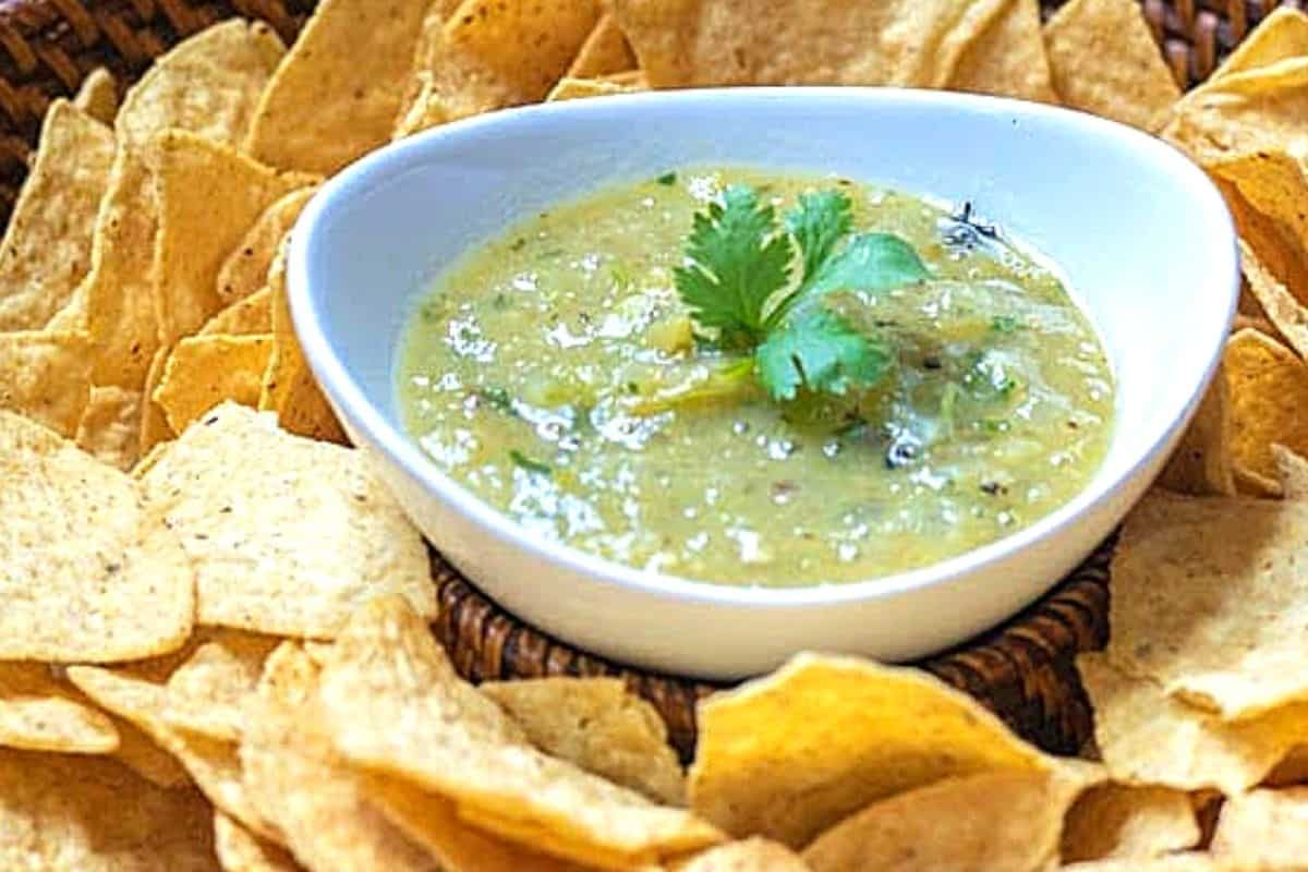 Bowl of Green salsa next to chips.