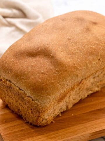 Loaf of wheat bread on cutting board.