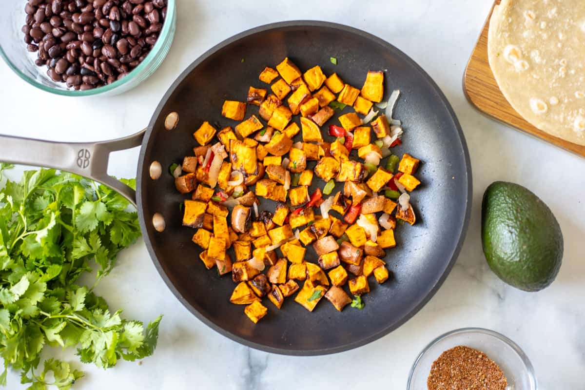 Cooked sweet Potatoes in skillet next to black beans and cilantro.