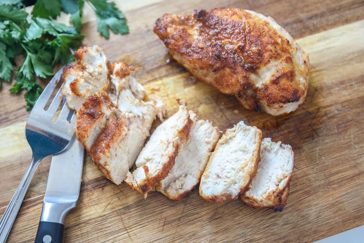 Sliced air fryer chicken breast on wooden cutting board.