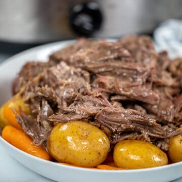 Close up of slow cooker pot roast on white platter with potatoes and carrots.
