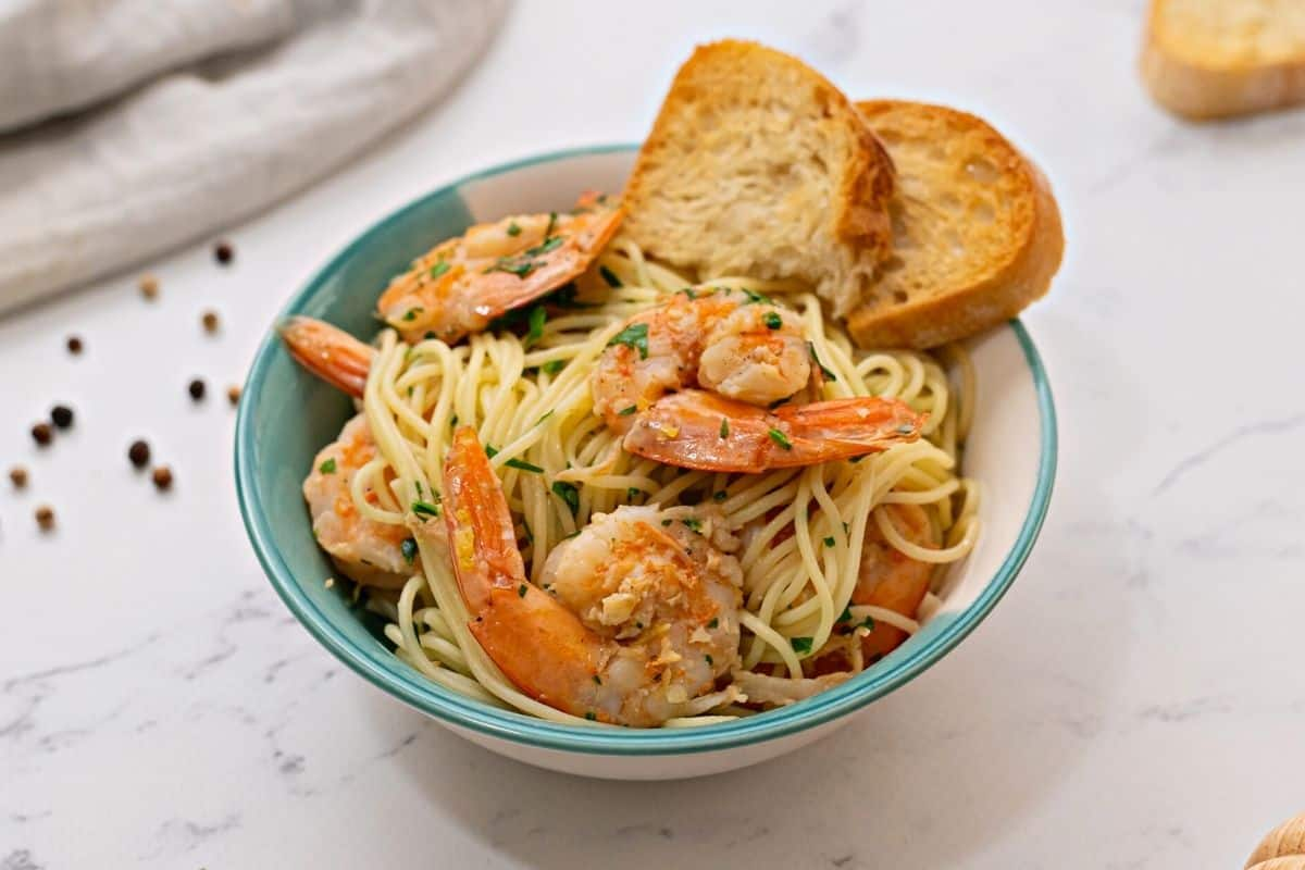 Shrimp Scampi Pasta in blue and white dish with garlic toast.