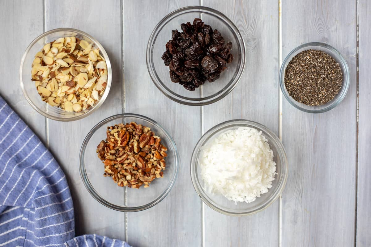 Bowls of nuts, coconut, chocolate chips, chia seeds, and raisins as optoins for granola mix-ins.