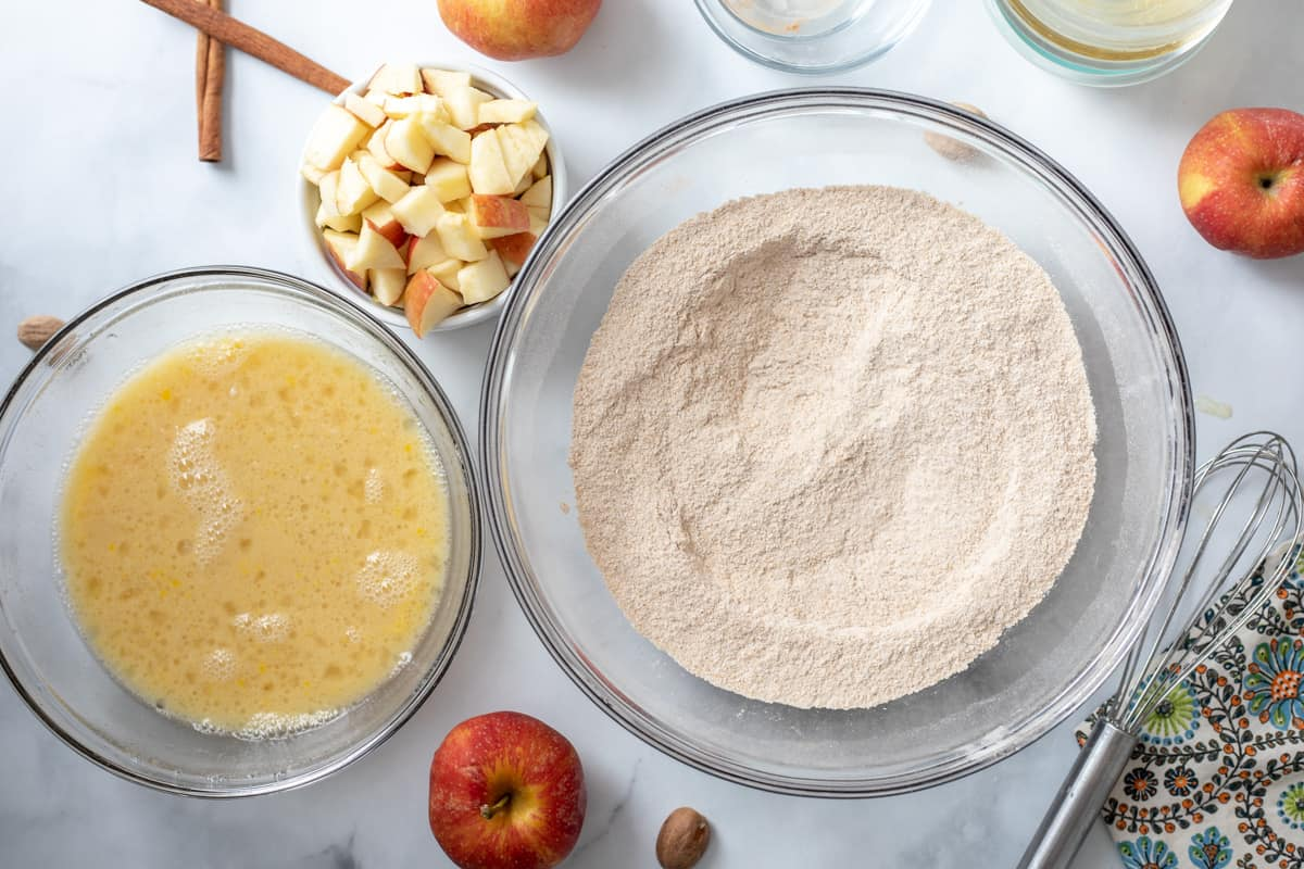 Mixing bowls with dry ingredients, wet ingredients, and apples.