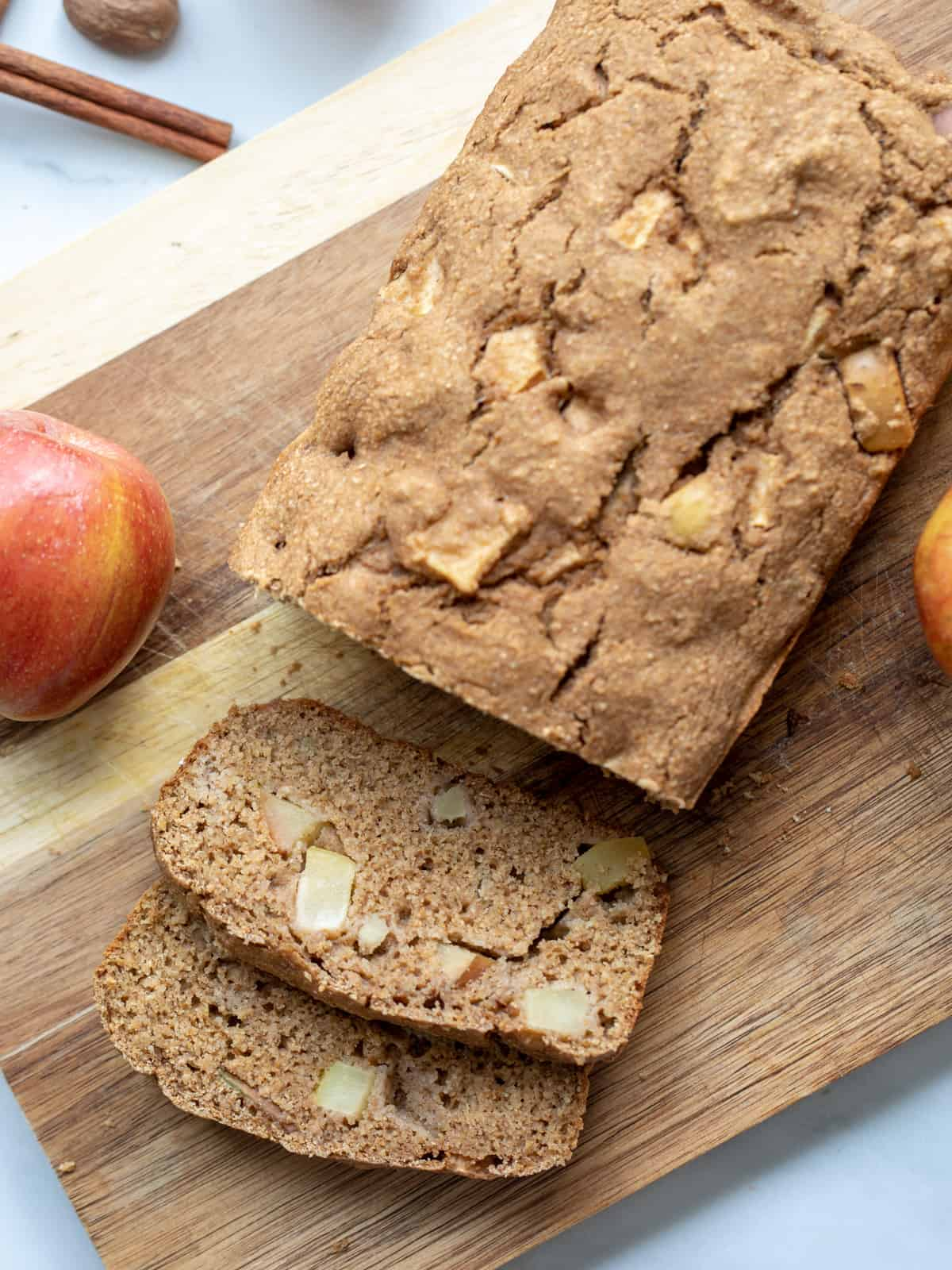 Loaf of apple bread on cutting board with 2 slices cut.