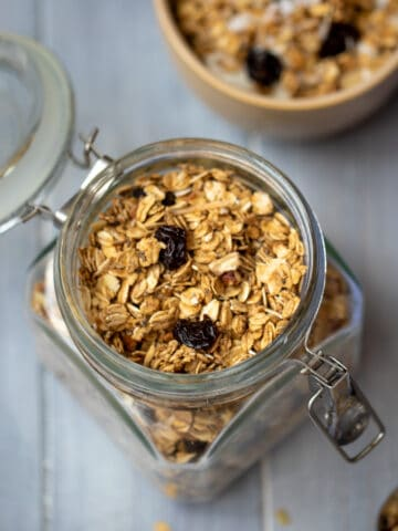 Homemade granola in jar with bowl of granola in background.
