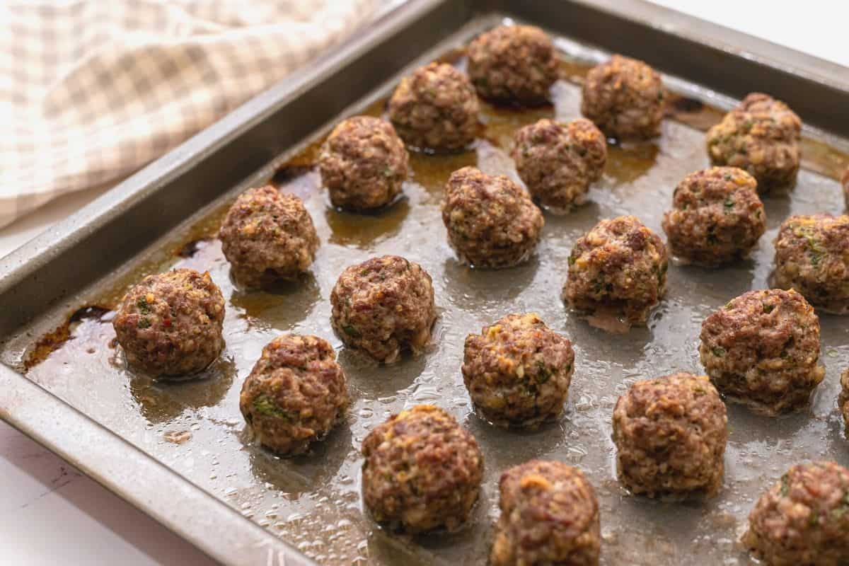 Sheet pan with baked meatballs.