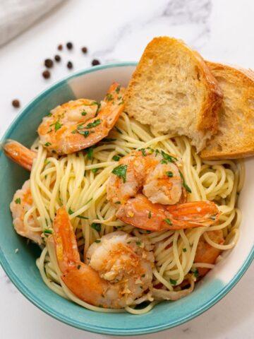 Bowl of shrimp scampi with garlic toast.