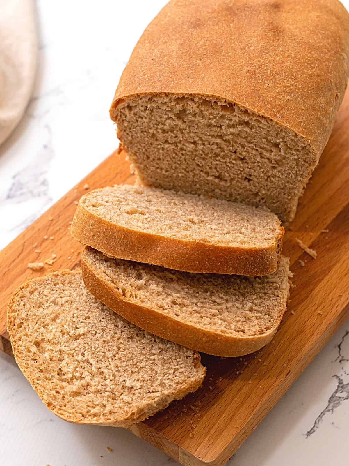 Loaf of whole wheat bread on cutting board with several slices cut.