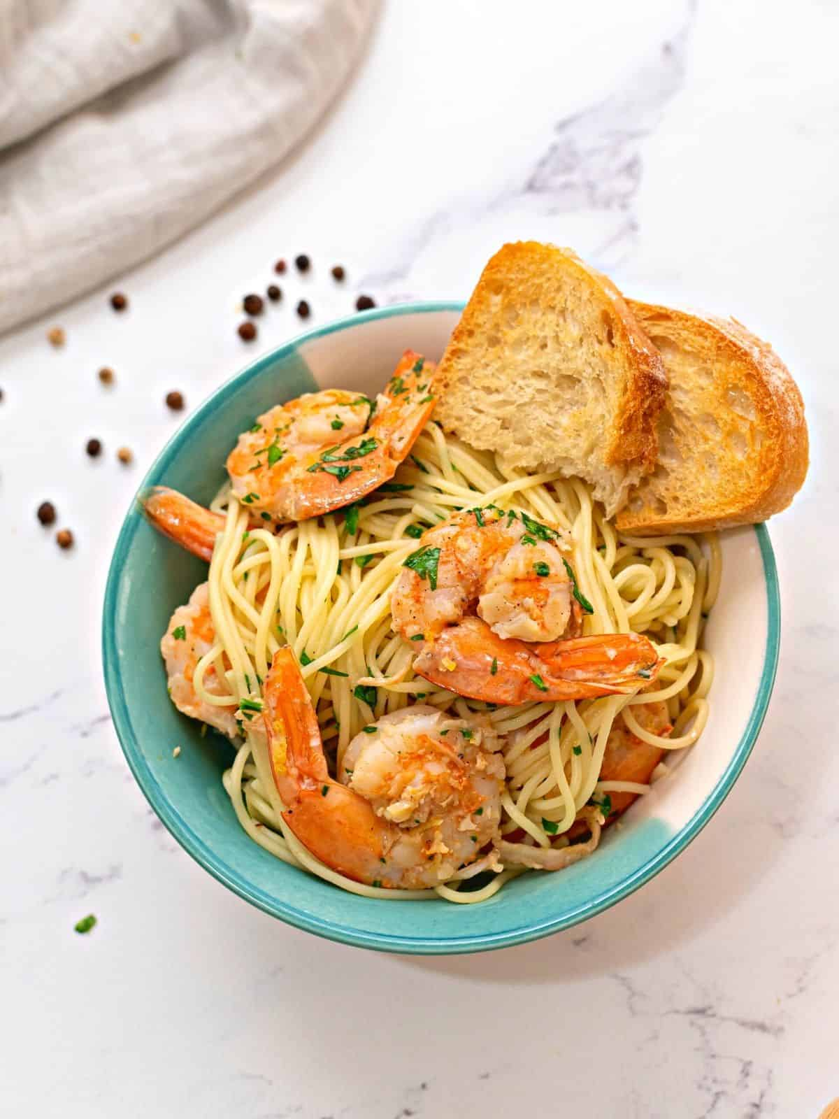 Bowl of Shrimp Scampi Pasta with garlic toast.