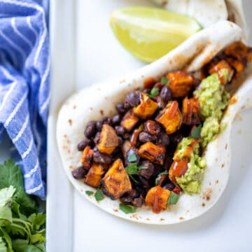 flour tortilla filled with sweet potatoes, black beans, and guacamole.