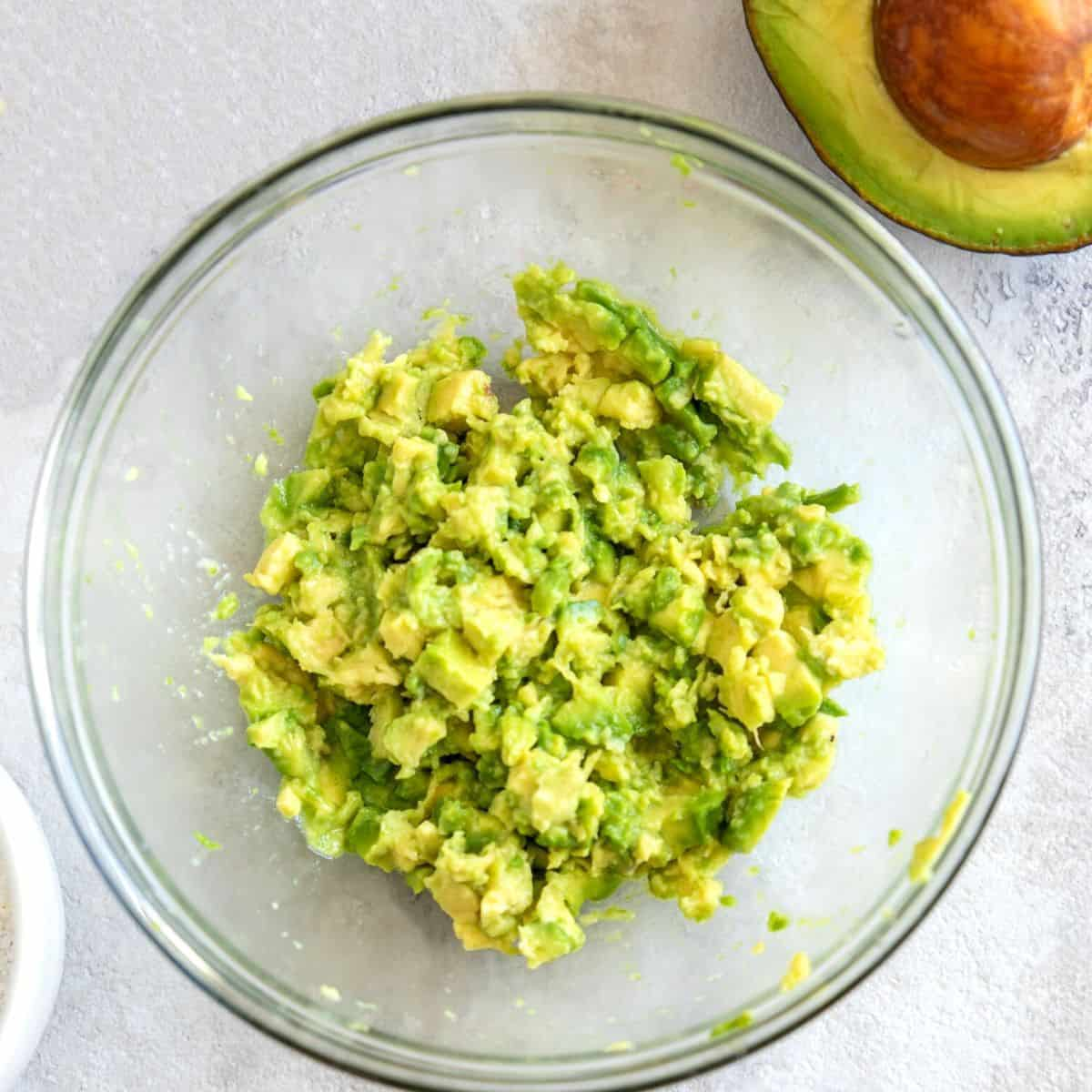 Mashed avocado in bowl with whole avocado next to it.