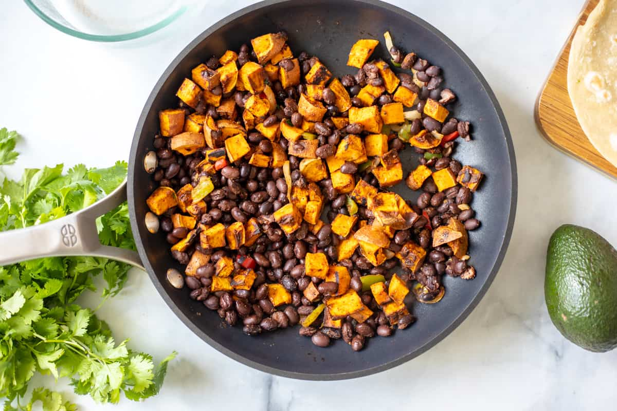 Skillet with sweet potatoes, black beans and taco seasoning.