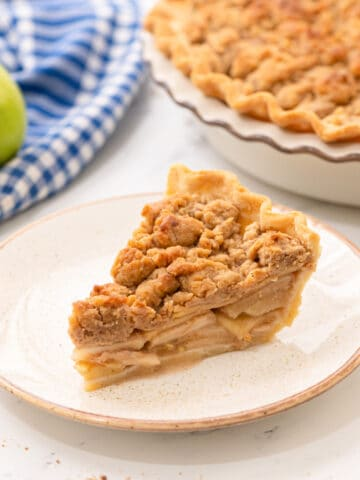 Slice of Dutch Apple Pie on White plate next to baked apple pie.