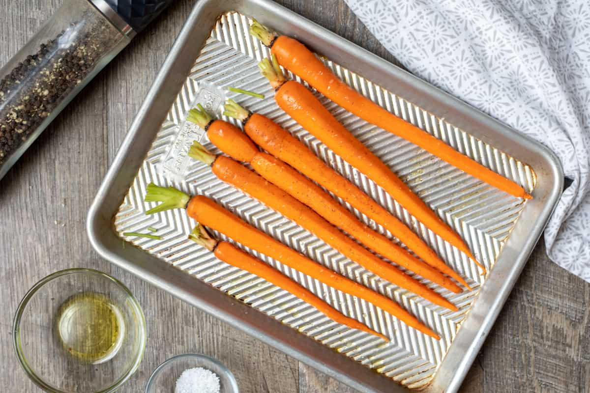 Seasoned raw carrots on baking sheet.