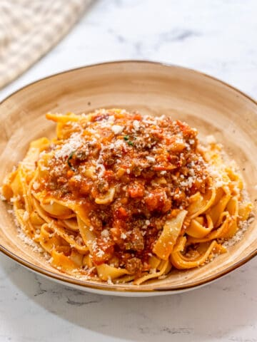 Pasta topped with bolognese sauce on cream plate.