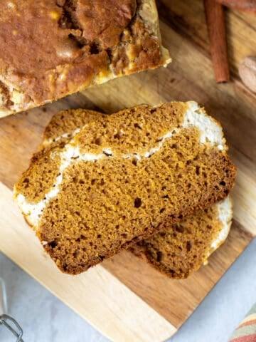 Slice of pumpkin bread on cutting board next to loaf of pumpkin bread.