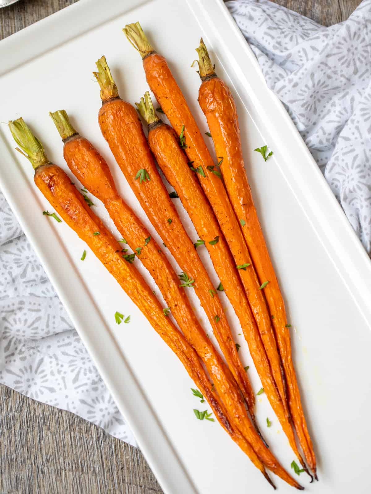 White serving dish with large roasted carrots.