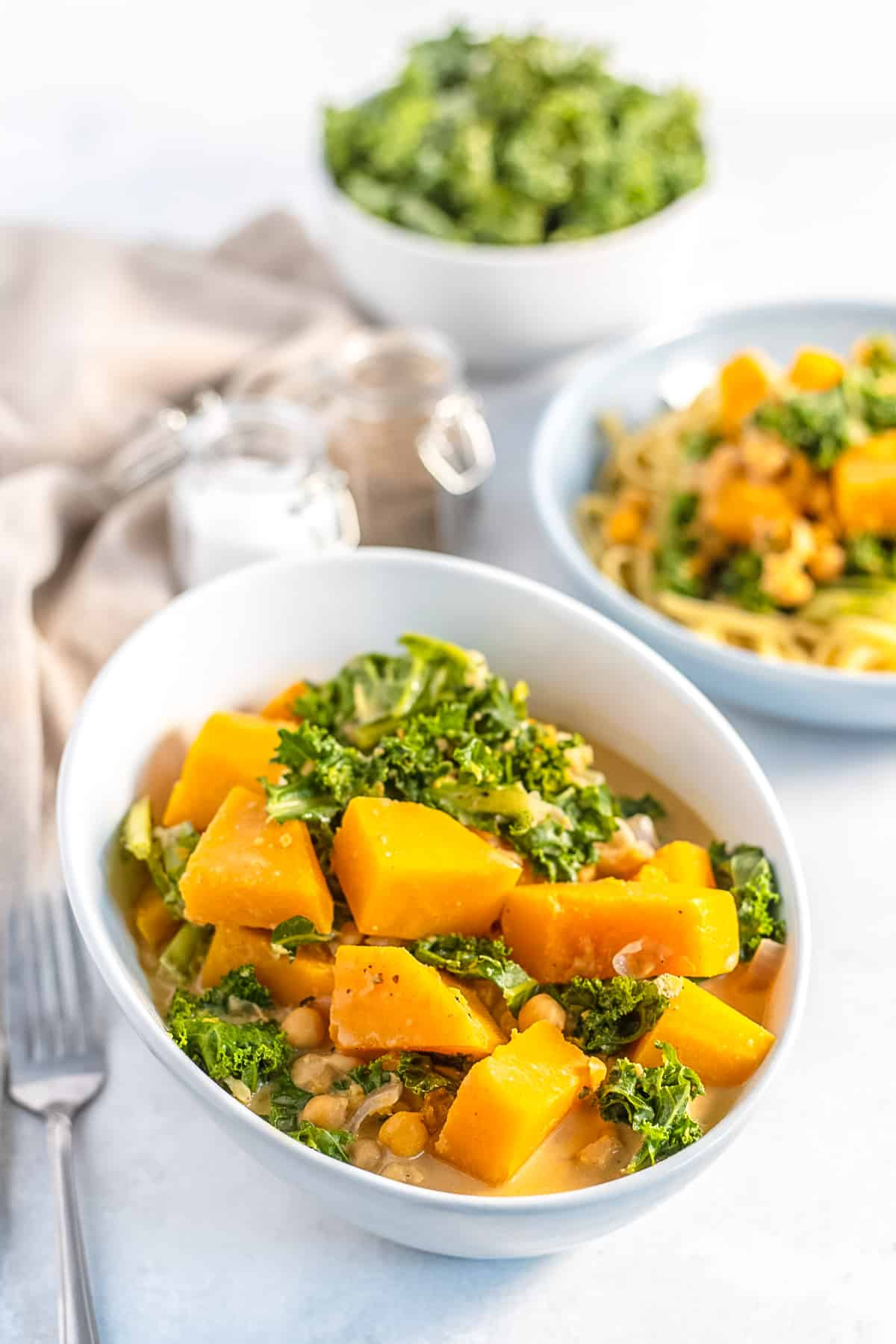 Bowl of vegetarian curry with butternut squash, kale, and chickpeas.