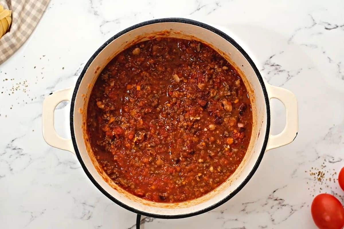 Bolognese Sauce simmering in dutch oven pan.