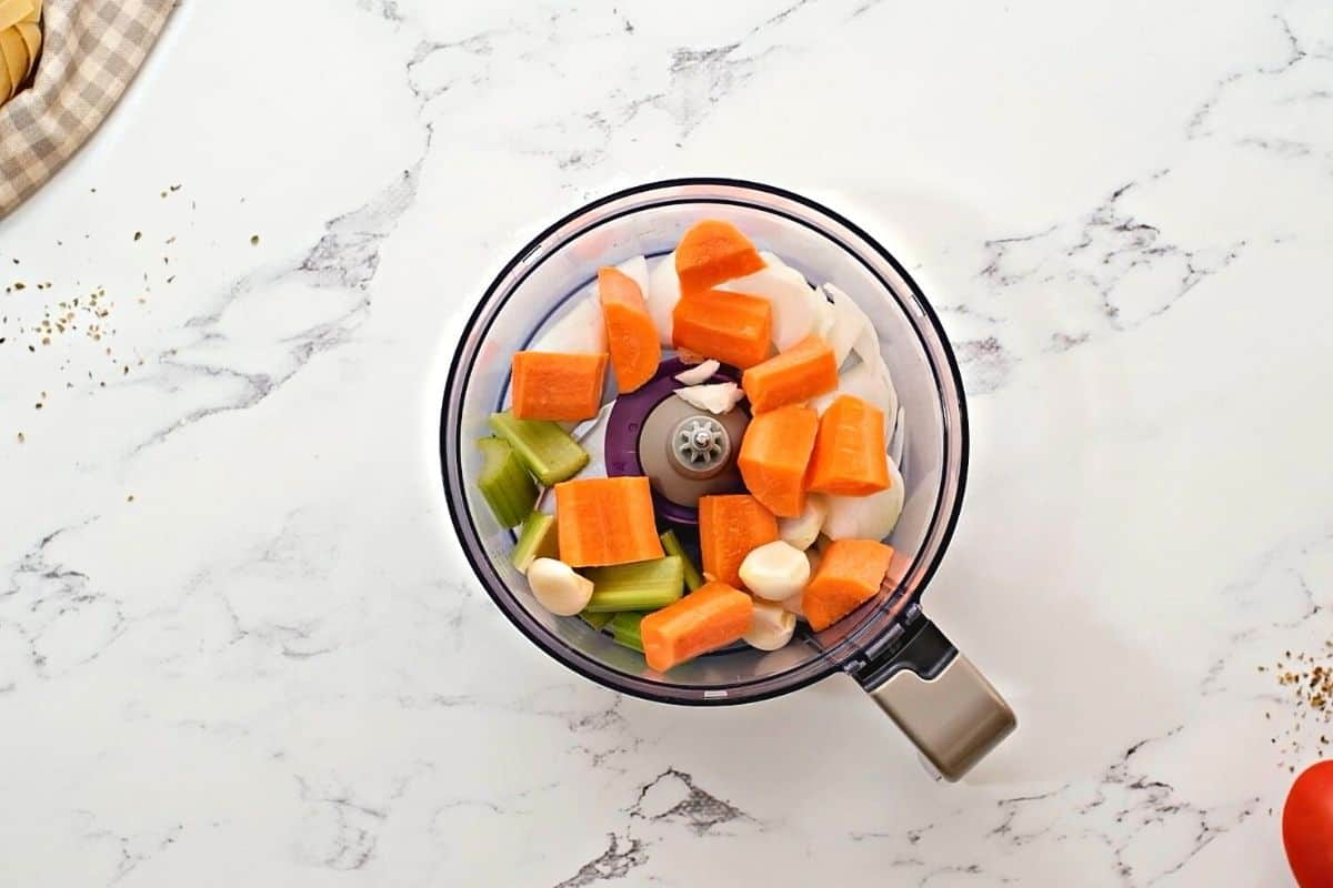 Carrots, onions, celery, and garlic in food processor.